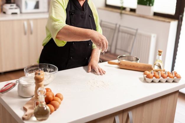 Процесс приготовления теста для домашнего хлеба. старший шеф-повар на пенсии с косточкой и фартуком, в кухонной униформе, рассыпание, просеивание, просеивание ингредиентов вручную, выпечка домашней пиццы и хлеба