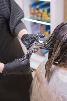 サロンで髪を着色するプロの美容師のプロセス
