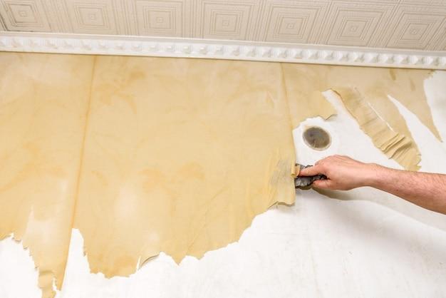 Процесс удаления старых обоев. очистка стены от мокрых старых обоев металлическим шпателем.
