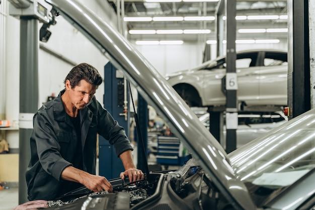 사고 후 자동차를 수리하는 과정. 차 근처에서 엔진을 가지고 작업하고 주의 깊게 검사하는 남자. 스톡 사진