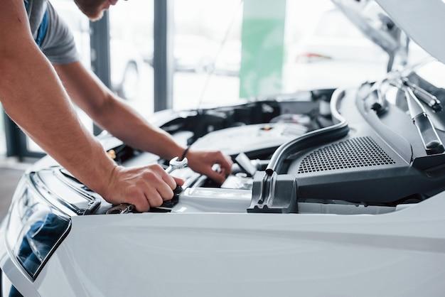 Процесс ремонта автомобиля после аварии. человек, работающий с двигателем под капотом.
