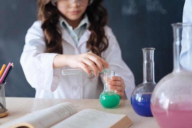 과학 협력의 과정. 과학 프로젝트에 참여하고 전구를 들고 실험실에 서서 화학 실험을 즐기는 똑똑한 창의적 참여 청소년