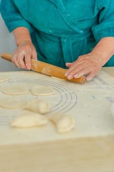 Процесс лепки отечественной вареники. бабушка готовит национальное украинское блюдо - вареники.