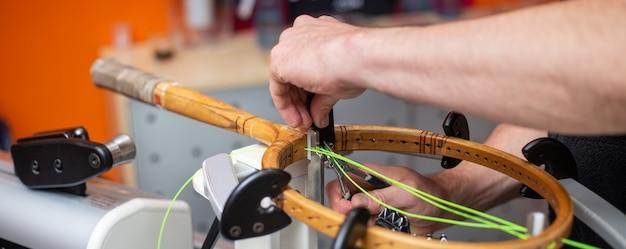 Процесс натягивания теннисной ракетки в теннисном магазине, концепция спорта и досуга, техническое обслуживание и настройка теннисной ракетки