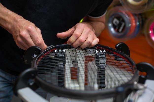 Процесс натягивания теннисной ракетки в теннисном магазине, концепция спорта и отдыха