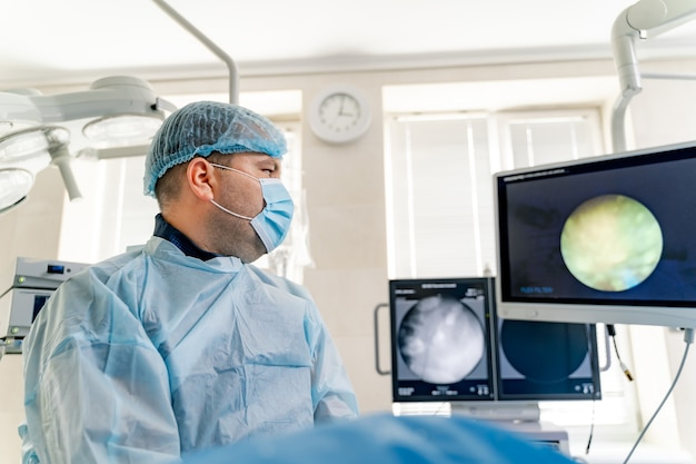 Процесс хирургической операции. хирург в операционной с хирургическим оборудованием. медицинское образование. выборочный фокус на мониторе для треккинга.