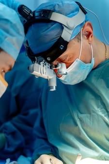 Процесс хирургической операции. хирурги в операционной с хирургическим оборудованием. медицинское образование, выборочный фокус