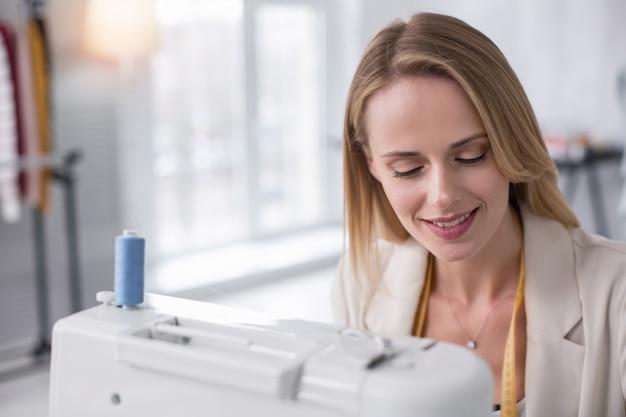 仕立てのプロセス。ミシンを使いながら笑顔の思いやりのある女性仕立て屋