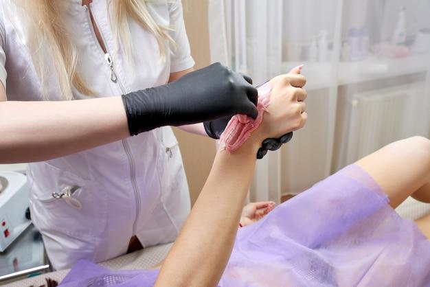 Процесс депиляции воском в салоне красоты профессиональным косметологом. работник салона красоты, применяющий воск и ленту для удаления волос с рук
