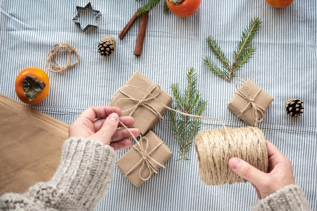 The process of packaging stylish modern gifts for christmas and new year. gift boxes made of kraft paper, twine and christmas tree branches. christmas background, holiday atmosphere.