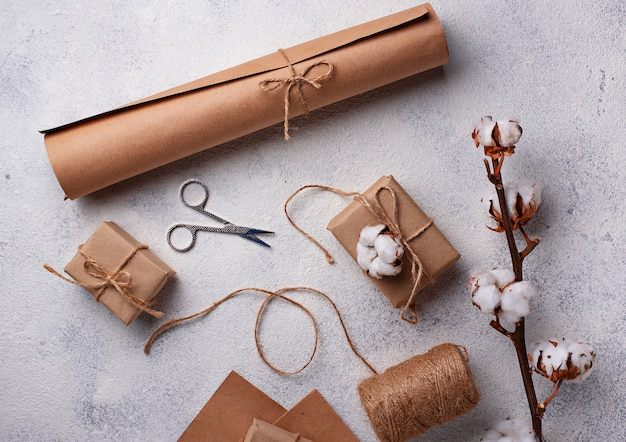Process of packing gifts boxes in craft paper.