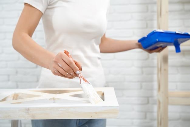 Процесс покраски деревянной стойки в белый цвет