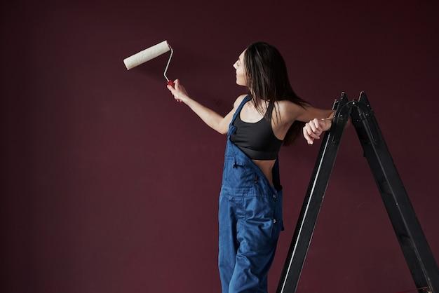 In fase di verniciatura. la giovane casalinga ha deciso di incollare la carta da parati nella sua nuova casa nella stanza