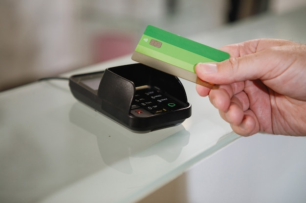 The process of paying with a contactless bank card with a plastic card in the store terminal.