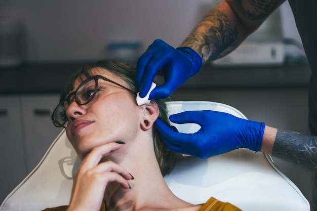 Process of piercing ear with steril neadle and latex gloves. ear piercing procedure