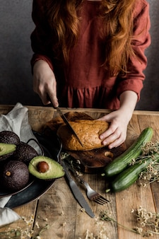 The process of preparing a healthy breakfast of bread and avocado on a wooden table.
