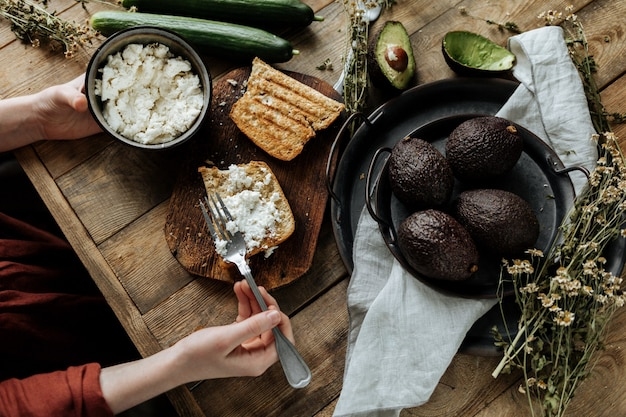 The process of preparing a healthy breakfast of bread, cottage cheese and avocado on a wooden table.