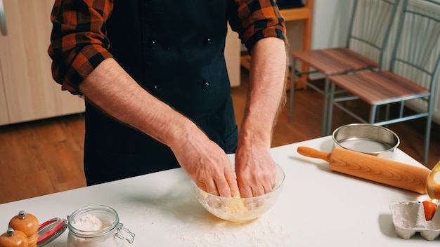 Process of preparing the pastry dough made by man baker. retired elderly chef with uniform sprinkling, sieving sifting raw ingredients by hand and mixing with flour for baking homemade pizza, bread.