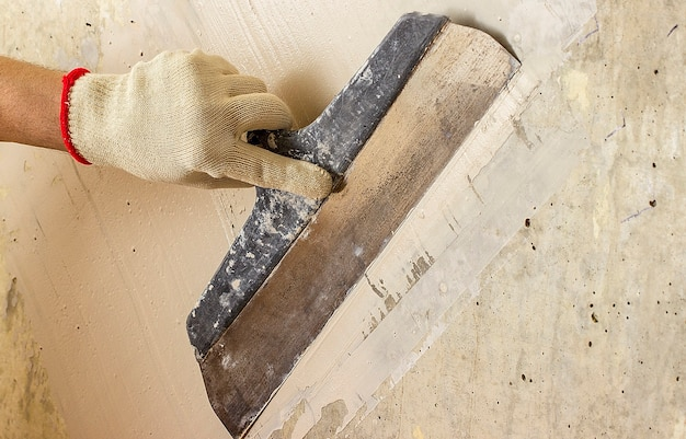 Process putty concrete wall with a metal spatula