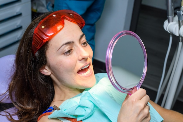 Process of removing dental braces from a caucasian girl in a dental clinic with a female dentist