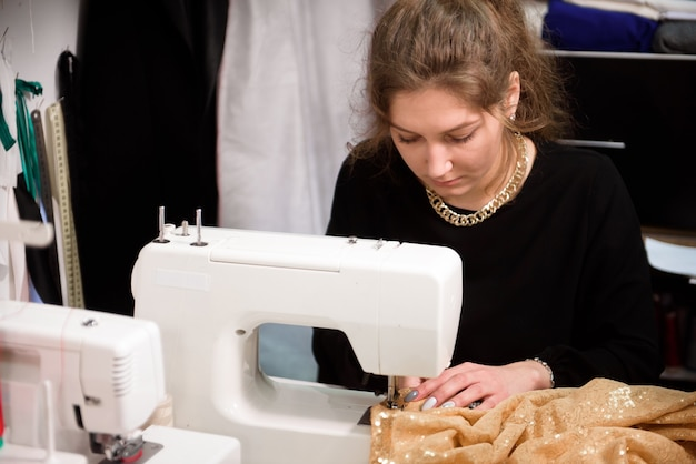 Process of sewing in atelier or workshop. tailoring and repair of clothing, self-employed employee.