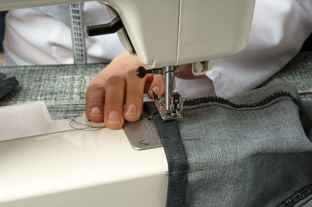 The process of shortening jeans pants on a sewing machine