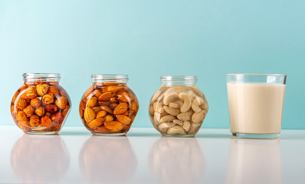 Process of soaking various nuts: almonds, hazelnuts, cashew in water to activate and glass of vegetable milk