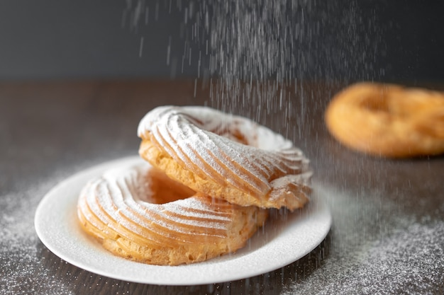 Process of sprinkling donuts with powdered sugar