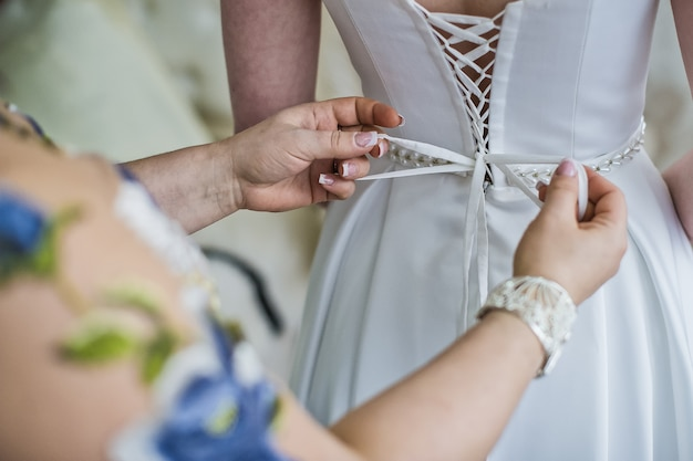 The process of tying a wedding dress, rear view
