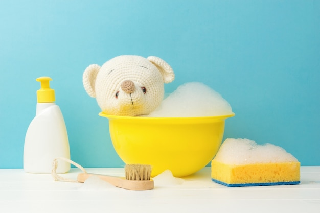 The process of washing a white bear cub and detergents on a white floor on a blue background.
