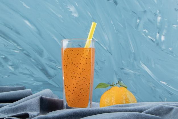 파란색 배경에 수건에 가공 주스와 레몬. 고품질 사진