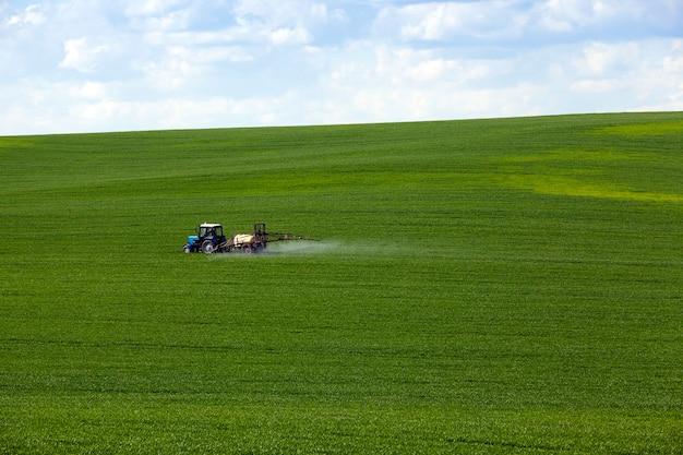 곡물 가공-트랙터, 농약 취급 중 농업 분야에서 촬영. 구름과 하늘