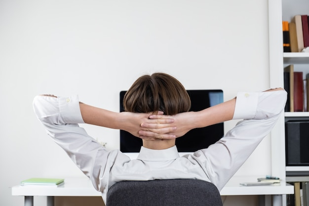Procrastination concept: office worker stretching in front of black computer screen. female employee sitting at desk and having rest at a workplace