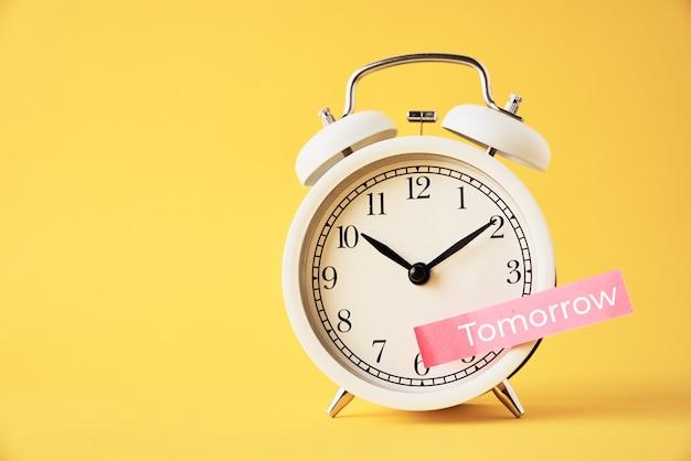 지연, 지연 및 연기 개념. 노란색 배경에 흰색 알람 시계에 내일 단어로 스티커 메모. 긴급 시간