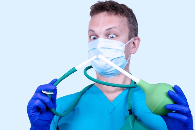 肛門科医、医療服の医者はゴム製の注射器を持っています