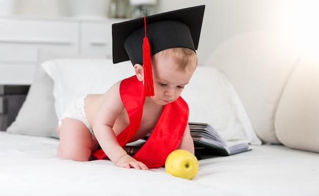 졸업 모자와 사과에 도달하는 빨간 리본에 신동 아기