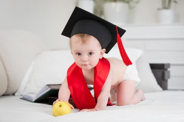 Вундеркинд в выпускной шапке тянется к яблоку