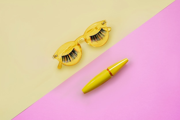 Product for eye makeup. mascara in yellow tube on pink and yellow sunglasses with long colored hairs lashes