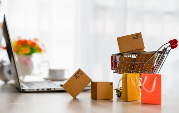 Product package boxes in cart and laptop on desk
