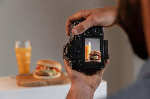 Продуктовый фотограф с камерой в студии