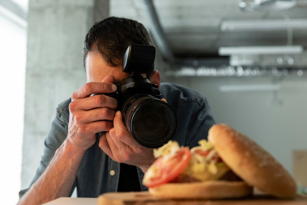 Product photographer with camera in studio