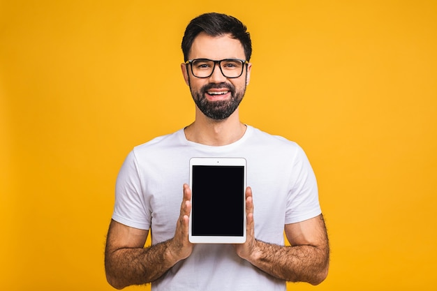 Product presentation. promotion. young bearded man holding in hands tablet computer with blank screen, close up. isolated over yellow background.