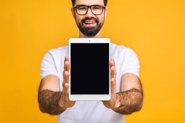 제품 발표. 프로모션. 빈 화면이 손에 태블릿 컴퓨터에 들고 수염 된 젊은이 닫습니다. 노란색 배경 위에 절연.