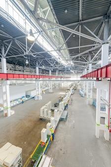 Производство и сборка бытовых холодильников на конвейерной ленте.