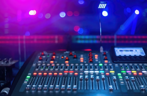 Production concept at the concert, a mixer for mixing music has lots of buttons with a blurred background in pink and blue tones.