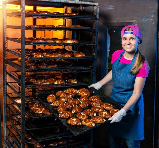 ベーキングケーキやパンの生産ライン。ペストリー付きラック。工場でトレイを持つ女性。閉じる。