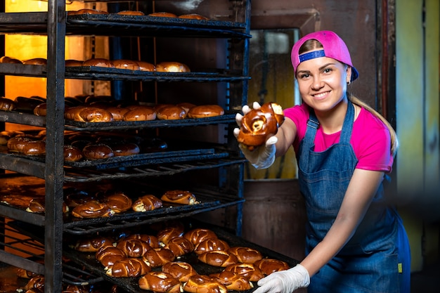 ベーキングクッキーの生産ライン。ペストリー付きラック。工場でトレイを持つ女性。閉じる。