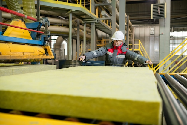 Production line worker in hardhat standing at conveyor belt and measuring construction material at factory