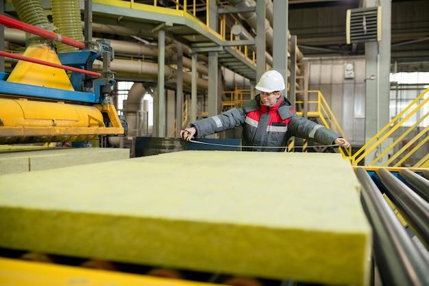 ベルトコンベアに立って工場で建設資材を測定するヘルメットの生産ライン労働者