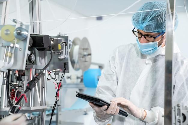 전자 공장에서 일하는 얼굴 마스크와 생산 라인 노동자